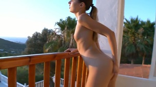 Young and slim chick Ivana meets the first ray of the sun with her naked sensitive boobs and wet pussy. She goes to the balcony and spreads her legs towards the sun!