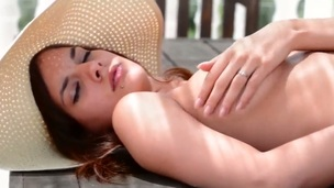 Astonishing bombshell Candice Luca in sexy hat spreads her beautiful long legs and caresses her beautiful shaved pussy sitting on the table with charming views of the lake.